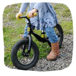 Ein Mädchen sitzt auf einem Laufrad
