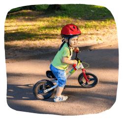 Ein Junge fährt auf einem Laufrad