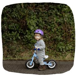 Ein Mädchen fährt auf einem Laufrad