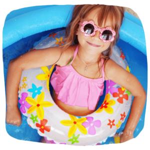Ein Mädchen liegt mit einem Schwimmreif und Sonnenbrille in einem Planschbecken